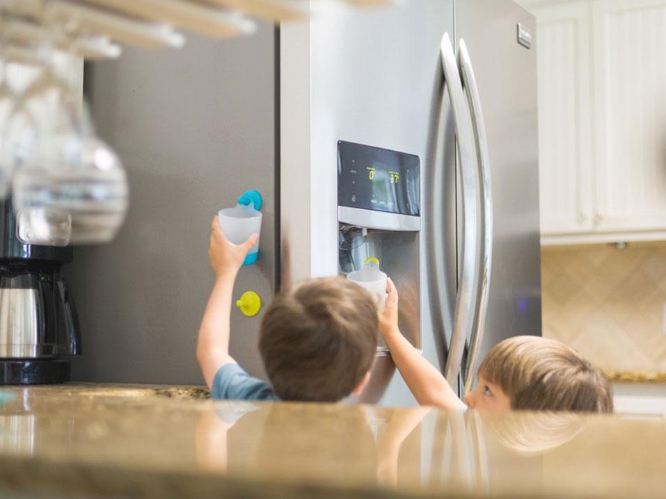 children reaching up to ice make on refrigerator